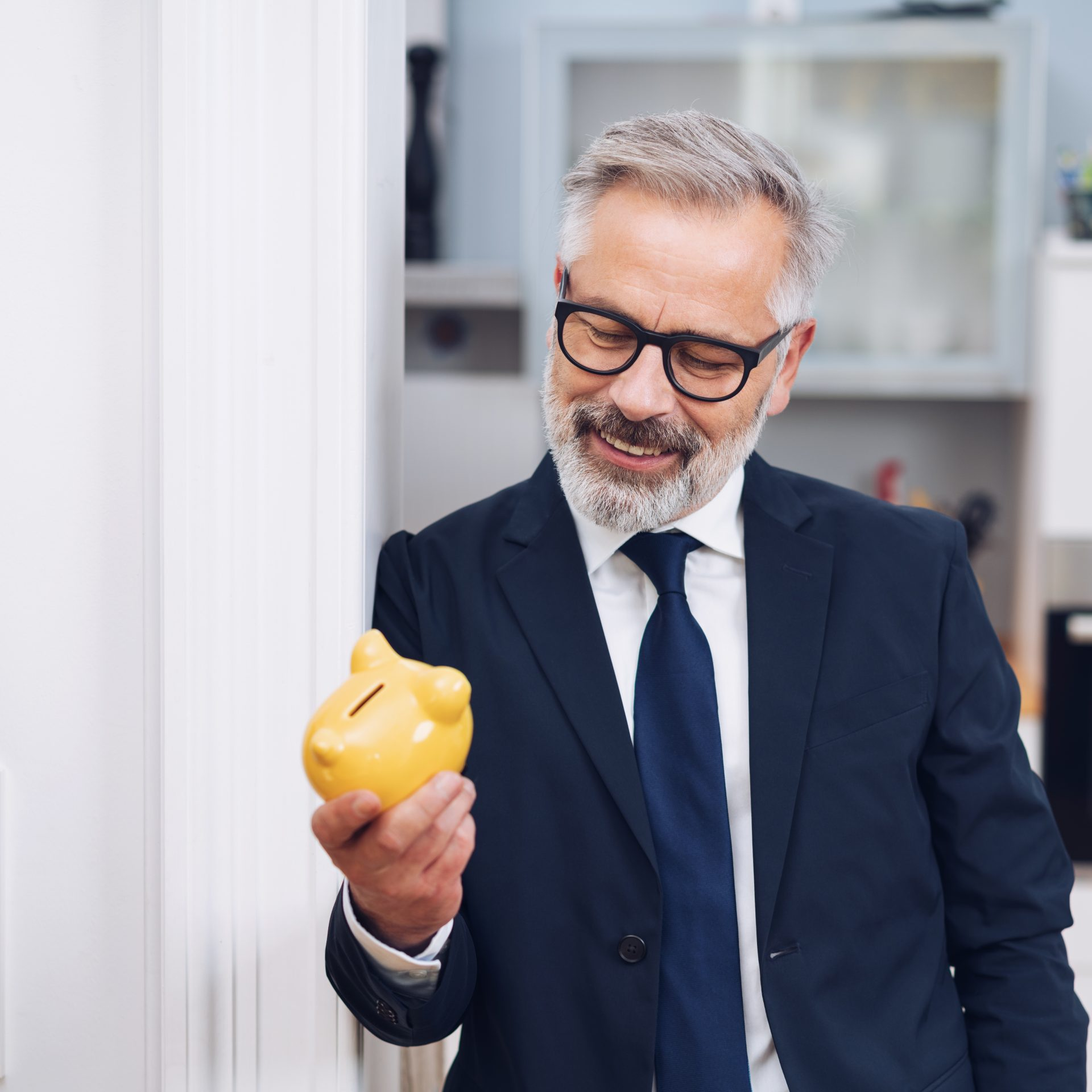 Successful businessman looking at a yellow handheld piggy bank with a pleased smile as he leans against a door frame at home